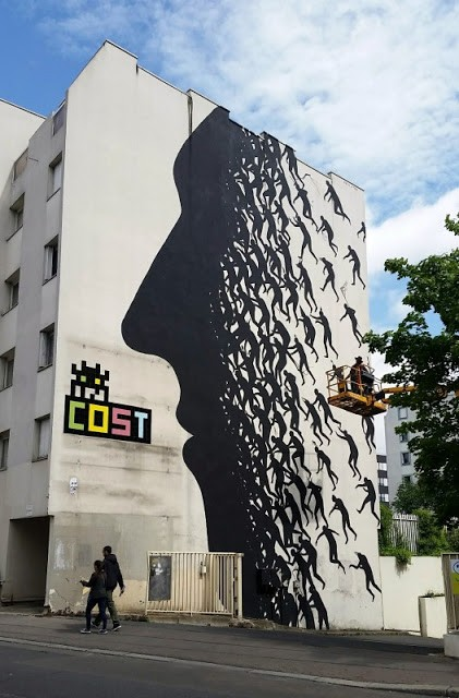 David De La Mano paints a large mural on the streets of Paris in France
