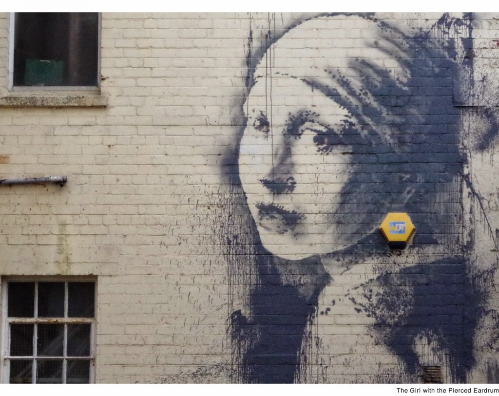 "Banksy paints ""The Girl With Pierced Eardrum"" at the Dockside Studios in Bristol, UK"