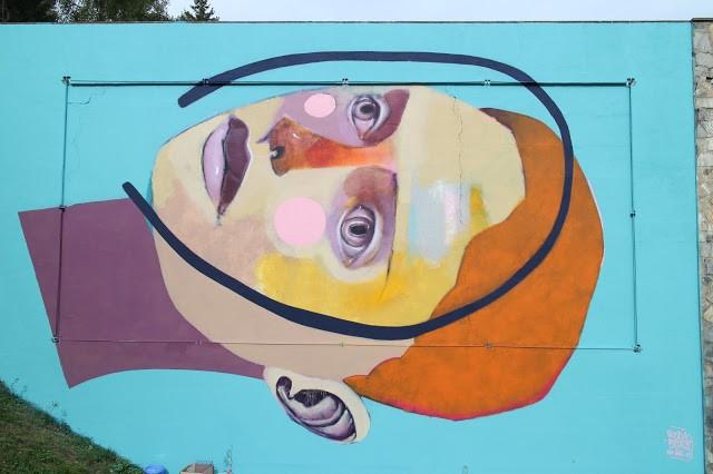 Rodrigo Branco paints a large portrait mural in Crans-Montana, Switzerland