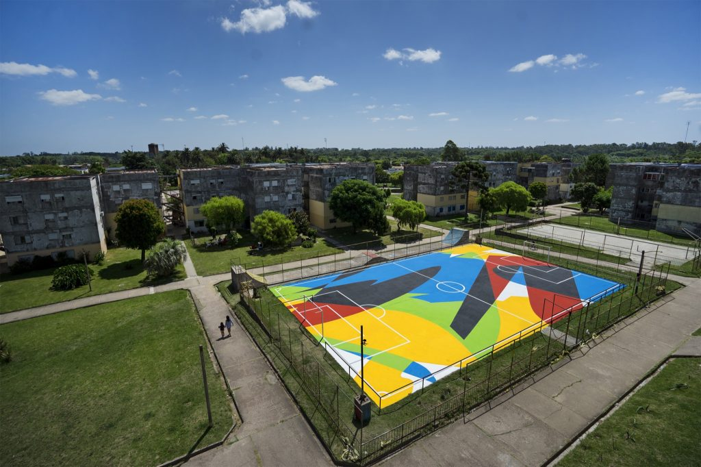 Elian paints a football court in Montevideo, Uruguay