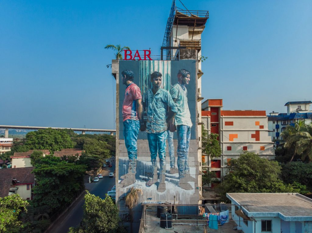 """Four Men Holding Roman column"" by Fintan Magee in Goa, India"